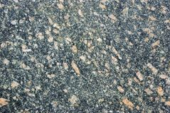 Old granite texture background. granite stone. dark gray granite with pink, yellow and white spots. Close up royalty free stock photography