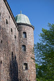 Old granite tower with green roof Stock Photo