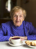 Old granny drinks black tea at the table. Stock Images