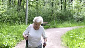 Old granny goes with sticks for walking on the road stock footage