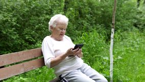 Old granny looks at Internet smartphone stock video