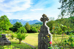 Old grave in cemetery. Orthodox cross tomb stone in graveyard, Europe. Old grave in cemetery. Vintage color tone Royalty Free Stock Images