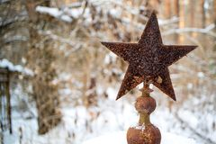 On the old grave an old rusty star of the Soviet period, the Red Army soldier is buried. On the old grave an old rusty star of the Soviet period, the Red Army stock images