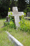 Old grave site. Old unattended grave with overgrown plants and weathered cross Royalty Free Stock Image