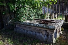 Old grave under a rosebush in a cemetery Stock Photography