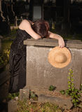 Old grave young widow. Gothic young girl crying on an old tombstone Royalty Free Stock Image