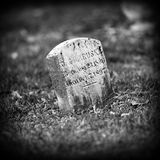 Old Gravestone. Old weathered gravestone in black and white stock photography