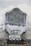 Old gravestone. Made of stone. Symbol of skull and crossbones is on the headstone. Tombstone is neglected, desolated and aged royalty free stock photo