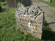 Old Gravestone With Skulls. A very interesting and decorative old gravestone. This grave marker has two skulls carved into the stone, these are surrounded by Royalty Free Stock Photos