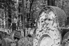Old gravestones in the New Jewish Cemetery in Miodowa Street, Kazimierz, Krakow, Poland. Gravestones amidst the undergrowth in the New Jewish Cemetery in stock photography