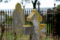 Old gravestones. Wales. Tombstones. Historic sculptures. Stone cross covered with moss. Old Welsh cemetery on the coast Royalty Free Stock Image