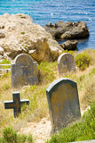 Old graveyard next to the water edge, rocks and sea of Malta Royalty Free Stock Images