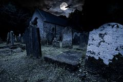 Free Old Graveyard With Ancient Tombstones Grave Stone And Old Church Front Of Full Moon Black Raven Dark Night Spooky Horror Royalty Free Stock Images - 160505359