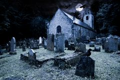 Free Old Graveyard With Ancient Tombstones Grave Stone And Old Church Front Of Full Moon Black Raven Dark Night Spooky Horror Royalty Free Stock Images - 160627469
