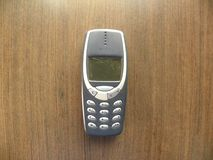Vintage mobile phone with keypad. Old gray color mobile phone with keypad kept on wooden table royalty free stock photos