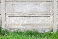 Old gray concrete fence stands on green grass. In summer park Stock Photos