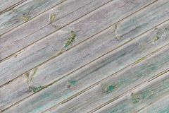 Old gray diagonal wooden boards with the remains of the green paint Stock Photos