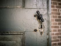 Old gray door with knob and lock hole stock photography