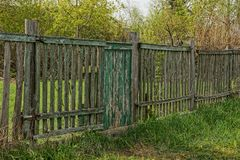 Old gray fence with green wicket in the grass Stock Photography