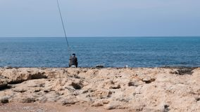 Old gray-haired fisherman in dark sweater and cap with fishing rod sitting on seashore and catching fish.  stock footage