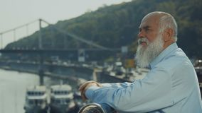 Old gray-haired man with beard relax near the river enjoying the view. Old gray-haired presentable man is outdoors in the city. Intelligent elderly man stands stock video footage