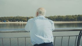 Old gray-haired man looks at the beach near the river. Old gray-haired presentable man is outdoors in the city. Intelligent elderly man stands near the railing stock video footage
