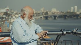 Old man near the river with phone. Old gray-haired presentable man is near the railing at the viewing place near the river. Intelligent elderly man looks at the stock video