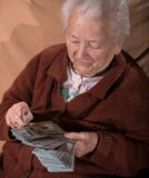 Old gray-haired woman holding dollar cash money Royalty Free Stock Images