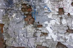 Old gray heavily damaged concrete wall with deep relief and protruding red bricks, cracks and various stains of paint. rough. An old gray heavily damaged royalty free stock image