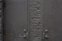 Old gray metal doors and bricks wall background Stock Photography