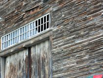 Old gray siding of old wooden barn peeling aound transom window above barn doors. Multi-pane window. grey to brown coloring, old New Englamd barn Middlesex Royalty Free Stock Image