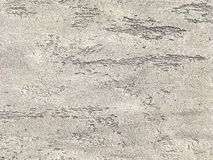 Old gray wall covered with shabby uneven plaster. Texture of vintage brown stone surface, closeup. Royalty Free Stock Image