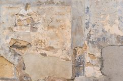 Old gray wall facade background with peeled stucco, close-up. Background texture of old damaged grunge wall facade with broken plaster, close-up royalty free stock image