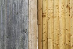 Old gray weathered fence planks and new light gold brown wood Stock Photo