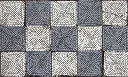 Old gray-white tile on a floor in chessboard order. Old mosaic gray and white tile on a floor, in a chess arrangement of colors. Some squares are broken or have Stock Photography