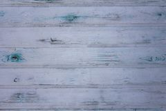 Old gray white wall fence of wooden planks with scratches and green blue stains of paint. horizontal lines. rough surface texture. A old gray white wall fence of stock photography