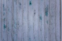 Old gray white wall fence of wooden planks with scratches and green blue stains of paint. vertical lines. rough surface texture. A old gray white wall fence of royalty free stock images