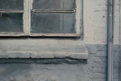 The old gray window on a brick painted house. The iron pipe royalty free stock photos