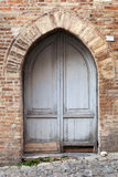 Old gray wooden door with arch in brick wall Royalty Free Stock Photography