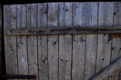 Old wooden gray door with hammered nails royalty free stock photography