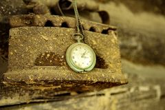 Old great grandmother`s iron and grandfather`s watch on chain hang on the wall in a village house. Closeup. Retro stock images
