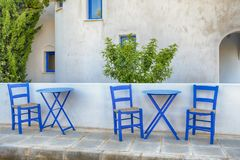 Old blue chairs with a wicker seat. Old greek blue chairs with wicker seating on a sun-drenched terrace at a vacation destination Stock Photos
