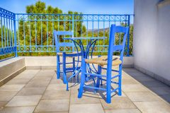 Old blue chairs with a wicker seat. Old greek blue chairs with wicker seating on a sun-drenched terrace at a vacation destination Stock Photo