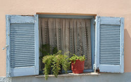 Old Greek Blue Window Shutters with pretty curtains Stock Photo