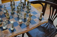 Old Greek chess figures on an antique chessboard. Old Greek chess figures antique armed warriors on the antique chessboard Stock Images