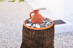 Old Greek clay jug on stones on the street.  Stock Photo