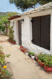 Old Greek house. Picture of old Greek house with flowers on the yard Stock Photo