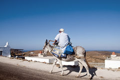 Old greek man in saddle to his donkey Royalty Free Stock Images