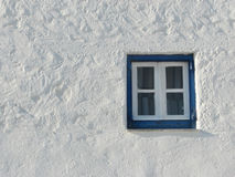 Old greek window. Details of traditional Greek Cycladic architecture - blue small window on a freshly whitewashed wall Royalty Free Stock Photo