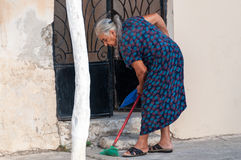 Old Greek woman is sweeping the sidewalk Royalty Free Stock Image